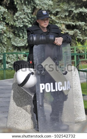 WARSAW, POLAND - MAY 11: Policewoman in riot gear, protecting a parliament building, during a protest of the Solidarity trade union against the pension reform on May 11, 2012 in Warsaw, Poland. - stock photo