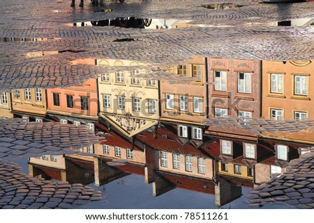 Warsaw, Poland. Old Town rain puddle reflection - tenements at the main square. UNESCO World Heritage Site. - stock photo