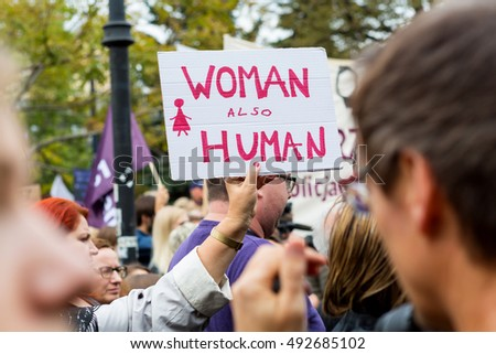 "Warsaw, Poland, 2016 10 01 - protest against anti-abortion law forced by Polish government; people with banner saying: ""woman also human"""