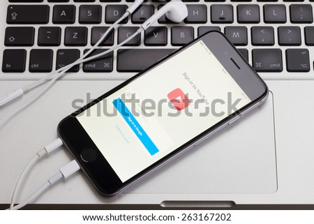 WARSZAWA, POLAND - DECEMBER 16, 2014. Apple Iphone 6 in gray space black color with youtube screen on macbook keyboard.  - stock photo