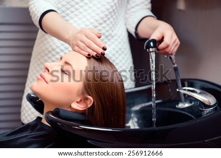 Wash away the stress. Cropped shot of a young woman having her hair washed at a professional hair salon - stock photo
