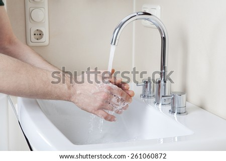 Wash hands with soap and water on a modern washstand - stock photo