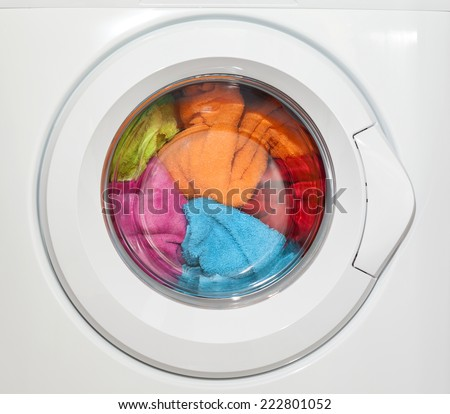 Wash machine with colored clothes inside - stock photo
