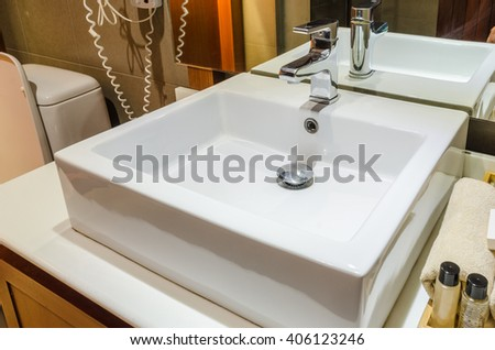 Washbasin and faucet in bathroom with amenities and towels