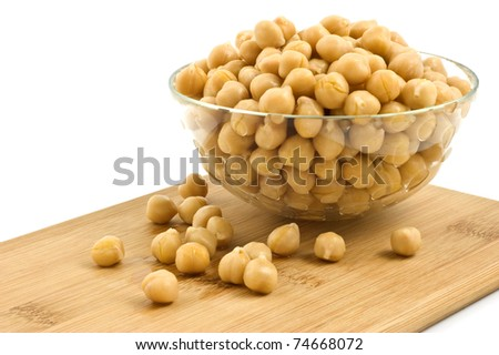 Washed and drained canned chick peas in glass dish on bamboo board isolated on white background