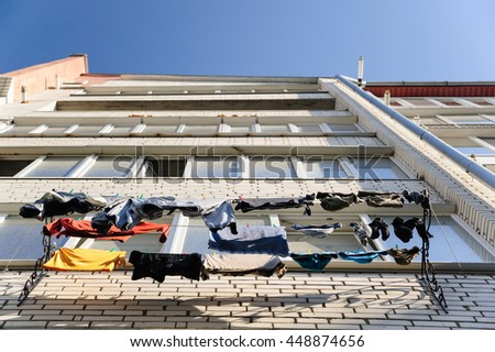 Washed linen is drying on the sun on the balcony of residential building - stock photo