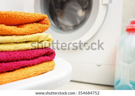washed towels stacked with washing machine in background - stock photo