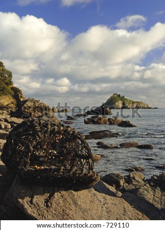 washed up crab pot infront of Thatcher rock torquay - stock photo