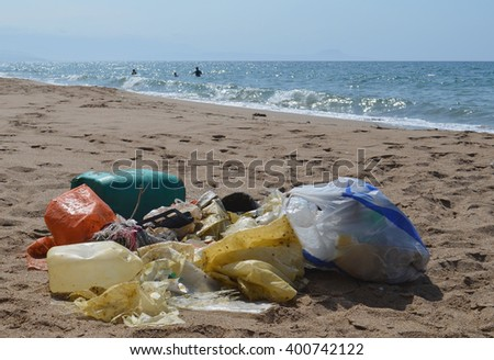 Washed up plastics on the beach while people play in the ocean