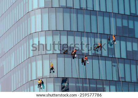Washers wash the windows of modern skyscrape