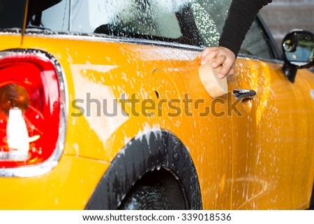 Washing a car with water and yellow hand soap - stock photo
