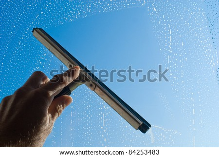 washing and cleaning the window with a squeegee - stock photo