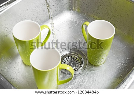 Washing bright green cups in the kitchen sink. Water running from the tap. - stock photo