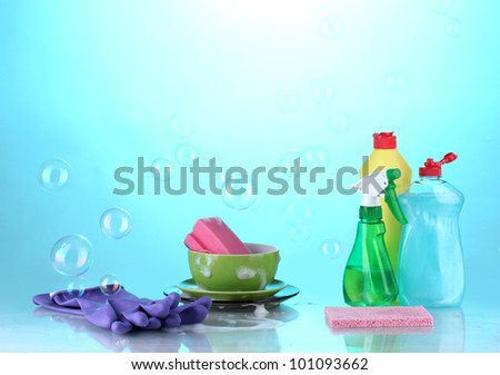 Washing dishes. Cleaning products  on bright blue background - stock photo