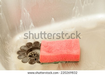 Washing dishes. Closeup of kitchen sink with foam sponge. Housework. Real. - stock photo