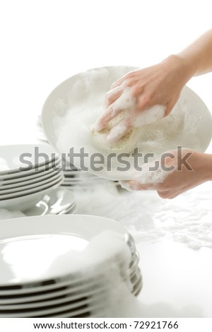 Washing dishes - hands with gloves in kitchen, housework - stock photo