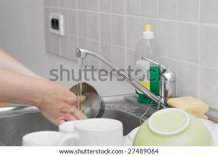 Washing dishes in the kitchen basin - stock photo