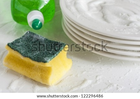Washing glasses and plates with detergent and water - stock photo
