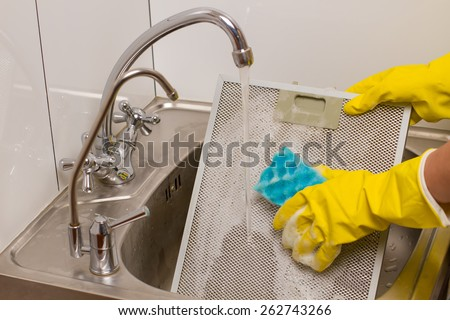 Washing grid kitchen hood in yellow gloves in the kitchen - stock photo