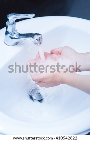Washing hands under flowing tap water - stock photo