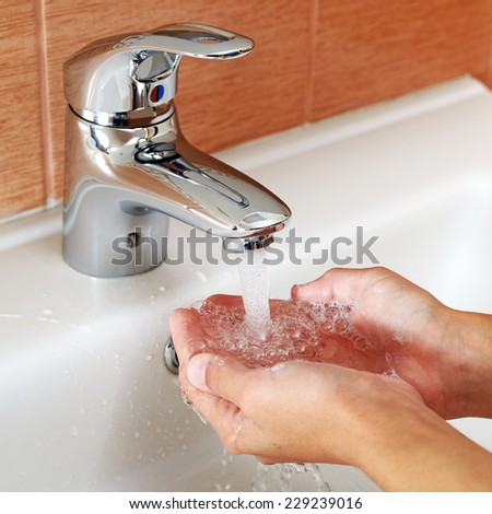 Washing hands under tap water - stock photo