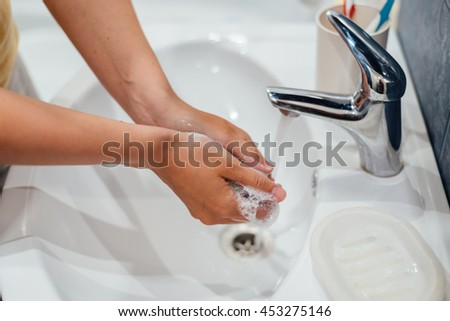 Washing hands with soap in bathroom, closeup