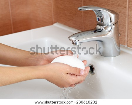 Washing hands with soap under tap water - stock photo