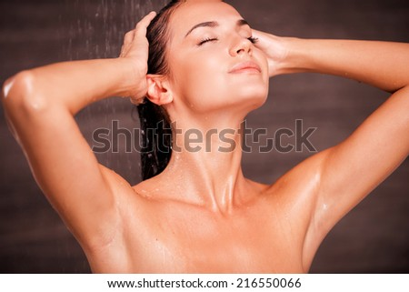 Washing her troubles away. Beautiful young shirtless woman standing in shower and washing hair - stock photo