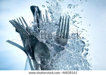 Washing kitchen ware in clear water on bubbles background