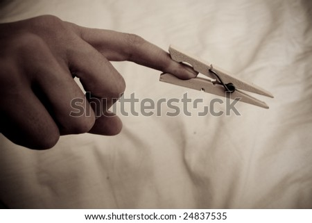 Washing line pin clamped to a finger - stock photo