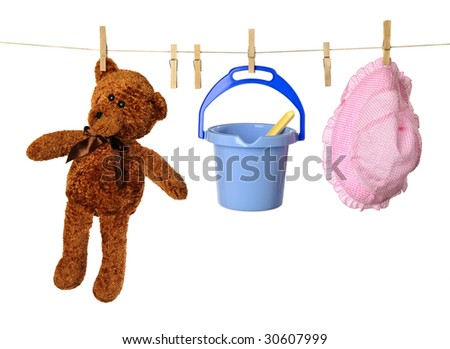 Washing line with childs holiday toys and teddy bear - stock photo