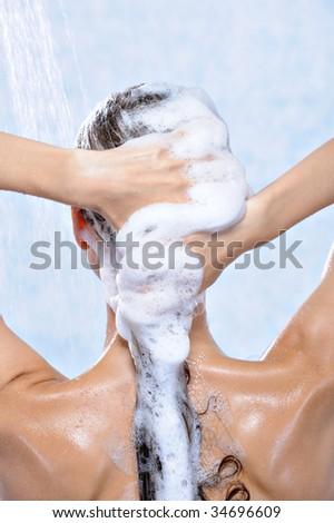 washing long brunette female hair by shampoo - close-up - stock photo