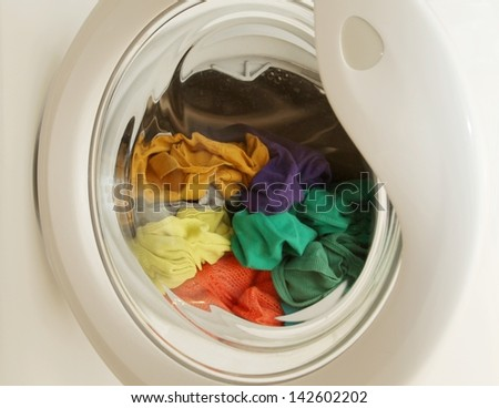 Washing machine full of dirty clothes - stock photo