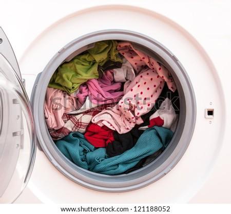 Washing machine full of dirty clothes, closeup - stock photo
