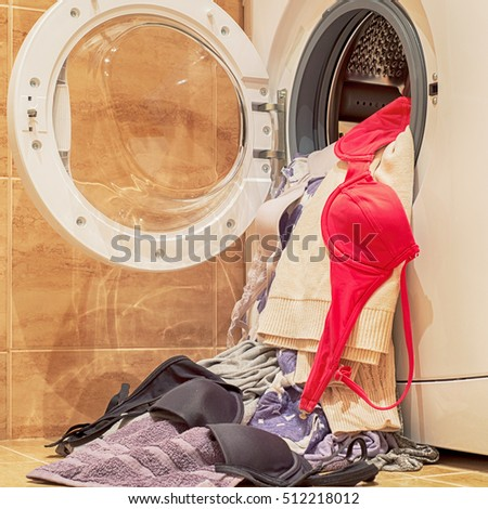 washing machine loaded with clothes, bras, blouses