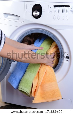 Washing machine loaded with clothes close-up - stock photo