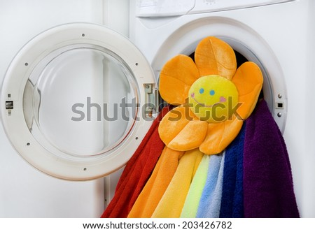 Washing machine, toy and colorful laundry to wash - stock photo