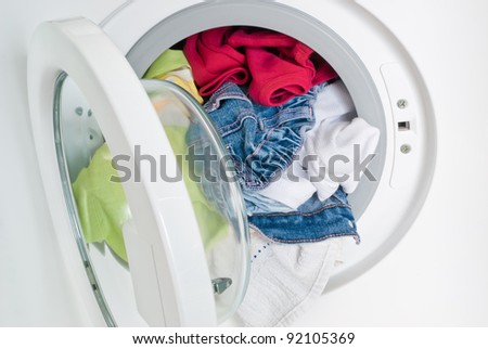 washing machine with colorful clothes inside - stock photo