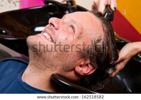 Washing man hair in beauty parlour hairdressing salon