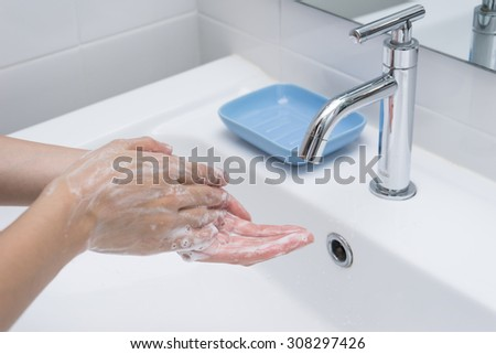 Washing of hands with soap under running water.
