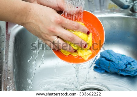 Washing of the dishes - woman hands rinsing dishes under running water in the sink  - stock photo