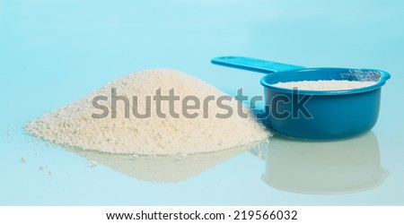 Washing powder and blue container on blue background - stock photo