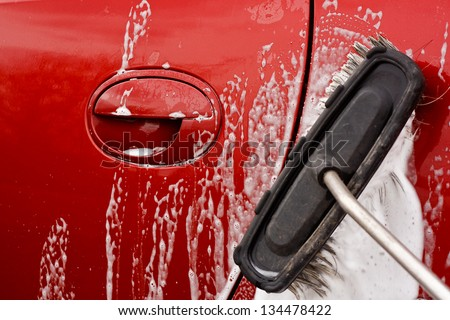 Washing the car with a soapy brush at a coin operated car jet wash - stock photo