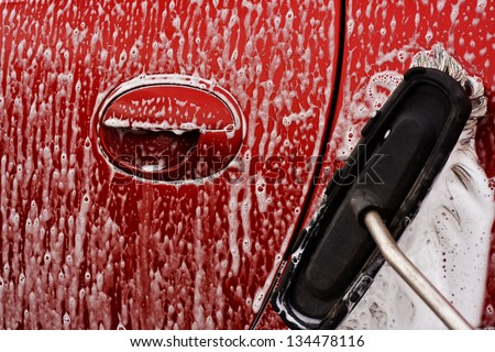 Washing the car with soapy soft brush at a car power wash - stock photo