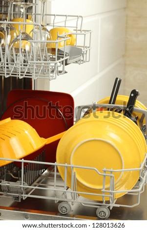 Washing the dishes: open full dishwasher, closeup - stock photo