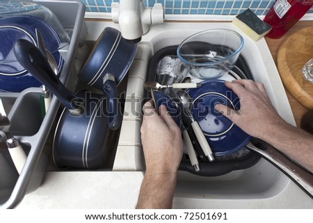 washing up a sink full of dirty dishes