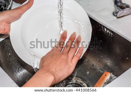 washing white dish with pouring water - stock photo