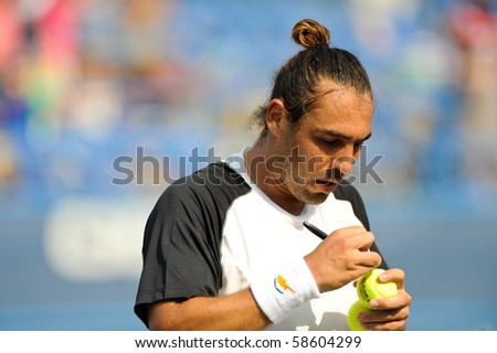 WASHINGTON - AUGUST 6: Marcos Baghdatis (CYP) autographs a ball after defeating Fernando Verdasco (ESP, not pictured) at the Legg Mason Tennis Classic on August 6, 2010 in Washington. - stock photo