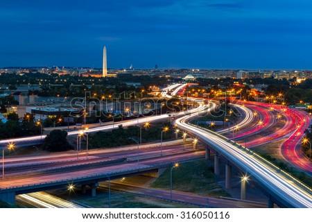 Washington D.C. cityscape at dusk with rush hour traffic trails on I-395 highway. Washington Monument, illuminated, dominates the skyline. - stock photo