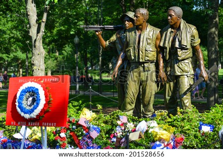 WASHINGTON, D.C. - MAY 26, 2014: People visit and lay flowers at the Vietnam Veterans Memorial during Memorial Day holiday on May 26, 2014, in Washington, D.C.  - stock photo